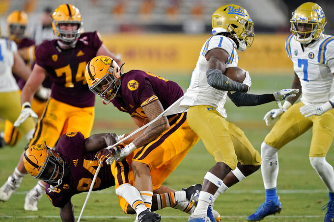 Arizona State wide receiver Frank Darby (84) pulls the shirt of UCLA defensive back Jay Shaw (1) after Shaw intercepted a pass during the second half of an NCAA college football game, Saturday, Dec. 5, 2020, in Tempe, Ariz. UCLA won 25-18. (AP Photo/Matt York)