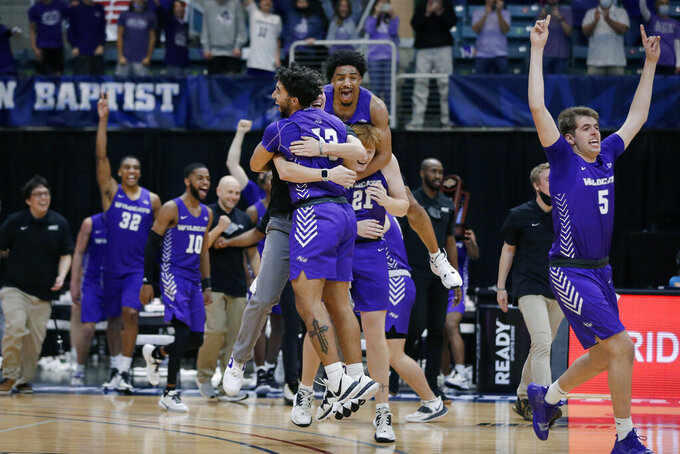 Abilene Christian players celebrate a 79-45 win against Nicholls State in an NCAA college basketball game for the Southland Conference men's tournament championship Saturday, March 13, 2021, in Katy, Texas. (AP Photo/Michael Wyke)