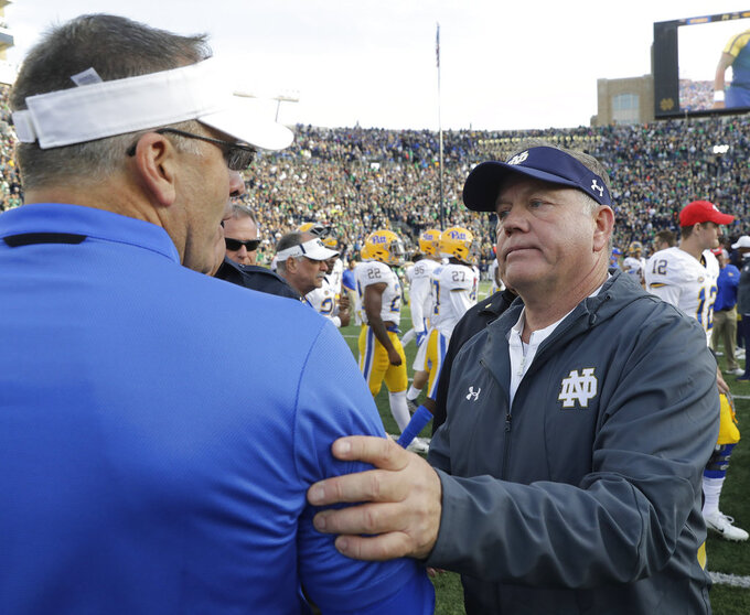 Notre Dame head coach Brian Kelly, right, talks with Pittsburgh head coach Pat Narduzzi following an NCAA college football game, Saturday, Oct. 13, 2018, in South Bend, Ind. Notre Dame won 19-14. (AP Photo/Darron Cummings)