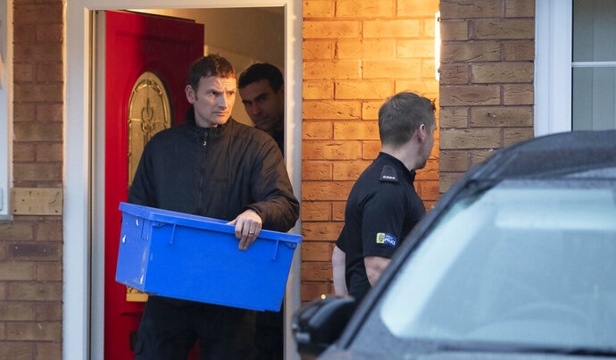 Police leave the home of Joanna and Thomas Maher with an evidence box at Wiltshire close in Warrington, Cheshire, Friday, Oct. 25, 2019, after a man and a woman, both aged 38 and from Warrington, have been arrested on suspicion of manslaughter and conspiracy to traffic people in connection with the 39 bodies found in a lorry in Essex on Wednesday. ( Jason Roberts/PA via AP)