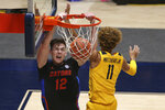Florida forward Colin Castleton (12) dunks on West Virginia forward Emmitt Matthews Jr. (11) during the second half of an NCAA college basketball game Saturday, Jan. 30, 2021, in Morgantown, W.Va. (AP Photo/Kathleen Batten)