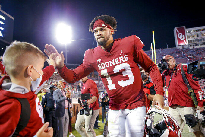 Oklahoma quarterback Caleb Williams (13) celebrates with fans while walking off the field after the team's team's 52-31 win over TCU in an NCAA college football game Saturday, Oct. 16, 2021, in Norman, Okla. (Ian Maule/Tulsa World via AP)