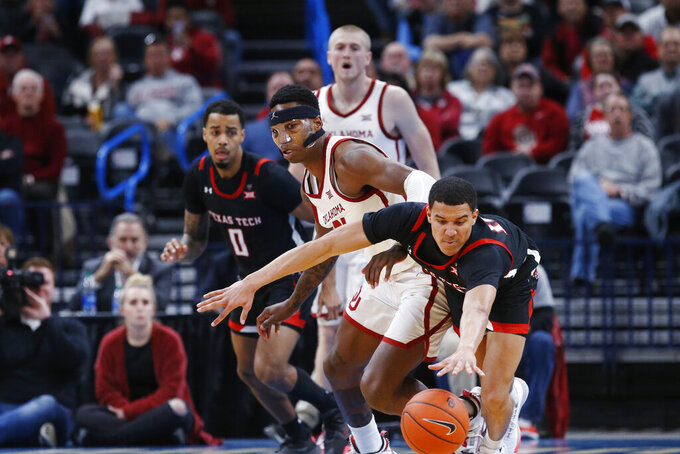 Texas Tech guard Kevin McCullar, right, reaches for the ball in front of Oklahoma forward Kristian Doolittle, left, in the second half of an NCAA college basketball game Tuesday, Feb. 25, 2020, in Oklahoma City. (AP Photo/Sue Ogrocki)
