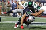 New York Jets defensive end Henry Anderson (96) and linebacker Harvey Langi, right, tackle New England Patriots wide receiver Julian Edelman in the first half of an NFL football game, Sunday, Sept. 22, 2019, in Foxborough, Mass. Edleman got up holding his rib area and left the game soon after. (AP Photo/Steven Senne)