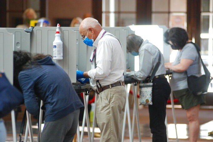 FILE - In this Oct. 6, 2020, file photo, temporary election worker Joseph Banar, center, disinfects voting stations as a precaution against the coronavirus while a steady stream of voters participates in the first day of balloting in New Mexico, at the Santa Fe Convention Center in Santa Fe, N.M. Democrat-backed efforts to expand voter access in New Mexico are coming to fruition, with the rollout of same-day voter registration this month. The first trial run took place in a low-turnout special congressional election June 1, 2021. (AP Photo/Morgan Lee, File)