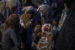 A woman collapses as refugees and migrants from the fire-destroyed Moria camp take part in a prayer on Lesbos island, Greece, Sunday, Sept. 13, 2020. Greek authorities have been scrambling to find a way to house more than 12,000 people left in need of emergency shelter after Moria camp was completed destroy by a fire. (AP Photo/Petros Giannakouris)