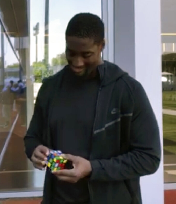 CORRECTS TO BEING CLAIMED OFF WAIVERS FROM THE PATRIOTS, NOT AS AN UNDRAFTED FREE AGENT FROM THE UNIV. OF TEXAS - In this image taken from video, New York Jets rookie offensive lineman Calvin Anderson works on a Rubik's Cube at the NFL football team's practice facility in Florham Park, N.J., Sunday, July 28, 2019. The puzzle cubes are a bit of an obsession for Anderson, who was claimed off waivers from the Patriots after New England signed him as an undrafted free agent. (AP Photo/Dennis Waszak)