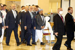 Abdullah Abdullah, center, chairman of Afghanistan's High Council for National Reconciliation, arrives wit his delegation for the opening session of the peace talks between the Afghan government and the Taliban in Doha, Qatar, Saturday, Sept. 12, 2020. (AP Photo/Hussein Sayed)