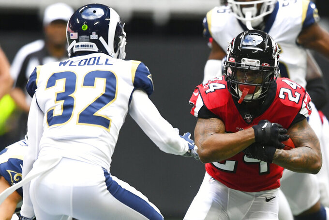 Atlanta Falcons running back Devonta Freeman (24) runs against Los Angeles Rams free safety Eric Weddle (32)during the first half of an NFL football game, Sunday, Oct. 20, 2019, in Atlanta. (AP Photo/John Amis)