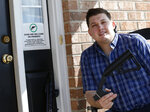 In this March 15, 2019 photo, Ryan Liskey displays a bump stock on the front porch of his home in Harrisonburg, Va. The ban on bump stocks is just a few days away and owners of the devices like Liskey are trying to figure out what to do. (AP Photo/Steve Helber)