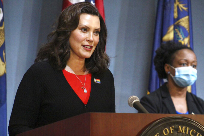 In this Friday, June 5, 2020 photo provided by the Michigan Office of the Governor, Michigan Gov. Gretchen Whitmer speaks in Lansing, Mich. Gov. Whitmer said Friday that barbershops and other personal-care businesses can reopen across Michigan on June 15, while those businesses and places like gyms and movie theaters that were shut down for months to curb the coronavirus can restart in northern Michigan next week. (Michigan Office of the Governor via AP, Pool)