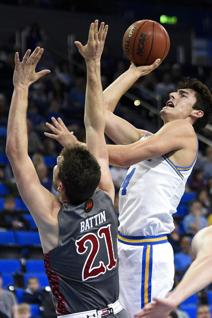 UCLA guard Jaime Jaquez Jr., right, shoots while Utah forward Riley Battin defends during the first half of an NCAA college basketball game in Los Angeles, Sunday, Feb. 2, 2020. (AP Photo/Kelvin Kuo)