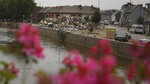 A pile of damaged household goods, discarded in the town square next to the river after flooding in Vaux-sous-Chevremont, Belgium, Saturday, July 24, 2021. Residents were still cleaning up after heavy rainfall hit the country causing flooding in several regions. (AP Photo/Virginia Mayo)