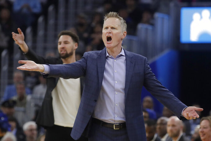 FILE - In this Dec. 28, 2019, file photo, Golden State Warriors head coach Steve Kerr, foreground, and injured guard Klay Thompson react to an official's call during the first half of an NBA basketball game against the Dallas Mavericks in San Francisco. It feels like so long ago that the Golden State Warriors even played a game. They missed going to the bubble in Florida, so it has been nine months. (AP Photo/Jeff Chiu, File)
