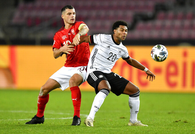 Germany's Serge Gnabry, right, and Switzerland's Granit Xhaka battle for the ball during the UEFA Nations League soccer match between Germany and Switzerland in Cologne, Germany, Tuesday, Oct. 13, 2020. (AP Photo/Martin Meissner)
