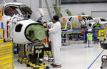 In this July 30, 2019, photo an employee works on an aircraft in the production area at the Honda Aircraft Co. headquarters in Greensboro, N.C. where the HondaJet Elite aircraft is manufactured. Nearly four years after delivering its first jet, Honda is facing decisions as the company better known for cars and lawnmowers considers whether to sink billions more into its decades-in-the-making aircraft division. (AP Photo/Gerry Broome)