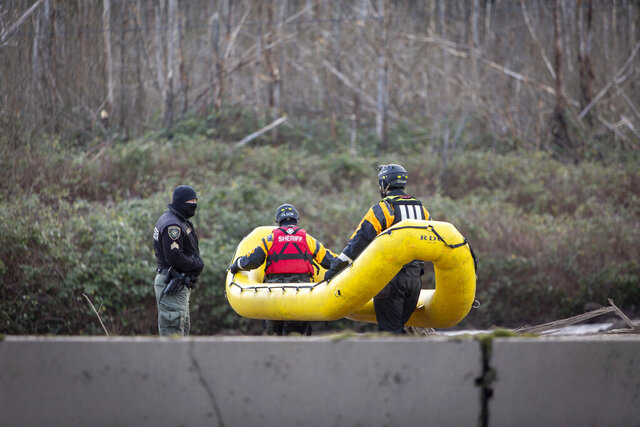 Search and rescue crews continue to look for a missing woman whose car was swept away by a mudslide Wednesday in the Dodson area of the Columbia River Gorge, in Oregon, Thursday, Jan. 14, 2021. Searchers used inflatable yellow rafts and drove metal poles into deep mud as they searched for a woman who was missing in Oregon during a powerful winter storm. Authorities have found part of the SUV that 50-year-old Jennifer Camus Moore was driving when she was swept away. (Brooke Herbert/The Oregonian via AP)