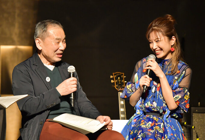 """In this photo provided by TOKYO FM, Japanese author Haruki Murakami, left, talks with guitarist Kaori Muraji during a show in Tokyo Sunday, Feb. 14, 2021. Murakami has a remedy for those who need relaxation from stress and worries in time of a pandemic - Brazilian Bossa nova music. During the approximately two-hour show, he recited his 1982 short story """"The1963/1982 Girl from Ipanema,"""" in which a narrator details his memory of his meeting with a metaphysical girl from the song, with live guitar performed by his guest Muraji. (TOKYO FM via AP)"""