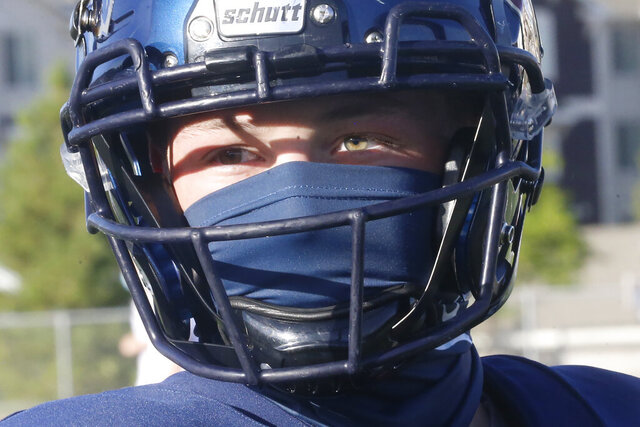 A Herriman player wear a mask during a high school football against Davis on Thursday, Aug. 13, 2020, in Herriman, Utah. Utah is among the states going forward with high school football this fall despite concerns about the ongoing COVID-19 pandemic that led other states and many college football conferences to postpone games in hopes of instead playing in the spring. (AP Photo/Rick Bowmer)