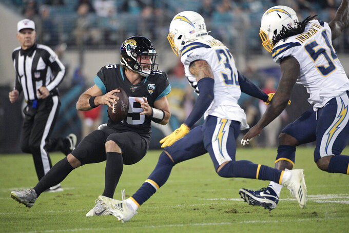 Jacksonville Jaguars quarterback Gardner Minshew, left, looks to pass as he is rushed by Los Angeles Chargers free safety Derwin James, center, and defensive end Melvin Ingram, right, during the second half of an NFL football game, Sunday, Dec. 8, 2019, in Jacksonville, Fla. (AP Photo/Phelan M. Ebenhack)