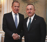 Turkey's Foreign Minister Mevlut Cavusoglu, right, and Russian Foreign Minister Sergey Lavrov shake hands before a meeting on the sidelines of the Munich Security Conference, in Munich, Germany, Saturday, Feb. 15, 2020.  Cavusoglu said the difference of opinion in Syria would not affect the Turkey-Russia relations.(Turkish Foreign Ministry via AP, Pool)