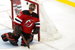 New Jersey Devils goaltender Scott Wedgewood (41) flips the puck up after making a save during the third period of an NHL hockey game against the Boston Bruins, Monday, May 3, 2021, in Newark, N.J. Wedgewood allowed three goals as the Bruins shut out the Devils. (AP Photo/Kathy Willens)