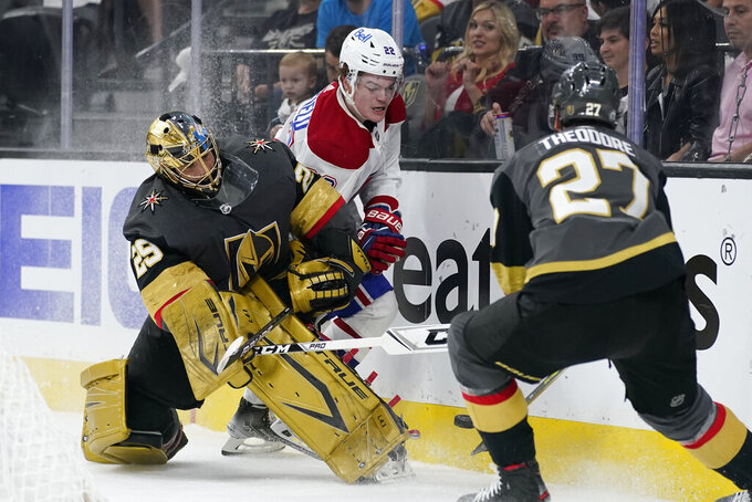 Vegas Golden Knights goaltender Marc-Andre Fleury (29) battles along the boards against Montreal Canadiens right wing Cole Caufield during the first period in Game 5 of an NHL hockey Stanley Cup semifinal playoff series Tuesday, June 22, 2021, in Las Vegas. (AP Photo/John Locher)