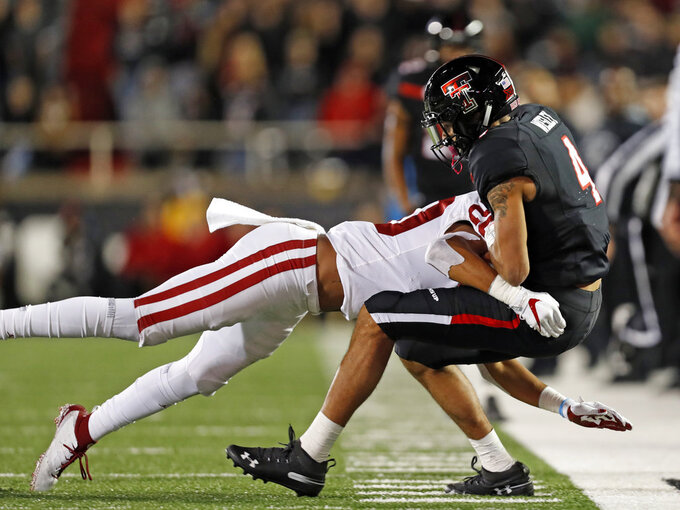 Texas Tech's Antoine Wesley (4) is tackled by Oklahoma's Robert Barnes during the second half of an NCAA college football game Saturday, Nov. 3, 2018, in Lubbock, Texas. (AP Photo/Brad Tollefson)