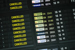 A departure timetable board displays cancelled flights at Brussels Airport in Brussels, Tuesday, May 12, 2020. Hard-hit by the coronavirus crisis, Brussels Airlines unveiled Tuesday a cost-cutting plan that will result in the reduction of 25 percent of its workforce. The Lufthansa subsidiary, which employs 4,000 people, has suspended its flights as a result of the pandemic, which has put much air travel to a halt. (AP Photo/Francisco Seco)