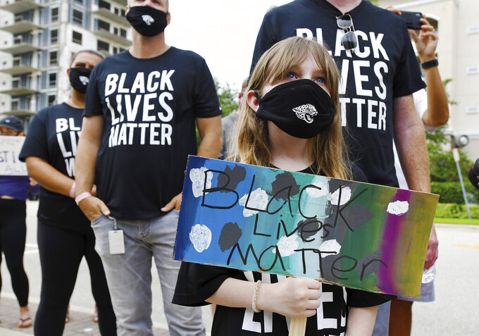 Caroline Youell, 9 holds her Black Lives Matter sign as she joins Jacksonville Jaguars NFL football players and their staff and families in a rally on the steps of the Jacksonville Sheriffs Office,  Friday morning, June 5, 2020, in Jacksonville, Fla., as they protest against inequality and police brutality. (Bob Self/The Florida Times-Union via AP)