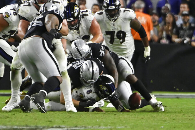 Las Vegas Raiders defensive end Carl Nassib (94) forces a fumble by Baltimore Ravens quarterback Lamar Jackson (8) during overtime in an NFL football game, Monday, Sept. 13, 2021, in Las Vegas. (AP Photo/David Becker)