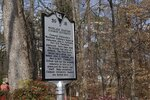 A marker stands at the entrance of Clemson's Woodland Cemetery in South Carolina on Sunday, Feb.  28, 2021, in Clemson, S.C.   Students at Clemson University who found an unkempt graveyard on campus last year sparked the discovery of more than 600 unmarked graves most likely belonging to enslaved Black people, sharecroppers and convicted laborers. The revelation has Clemson working to identify the dead and properly honor them amid a national reckoning by universities about their legacies of racial injustice.  (AP Photo/Michelle Liu)