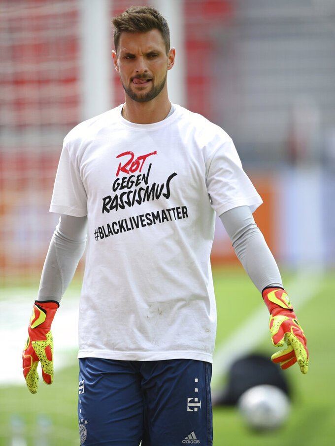 Goalkeeper Sven Ulreich of Muenchen wears a shirt with a message reading 'Red against racism #blacklivesmatter' as he warms up before the German Bundesliga soccer match between Bayer Leverkusen and Bayern Munich in Leverkusen, Germany, Saturday, June 6, 2020. (Matthias Hangst, Pool via AP)