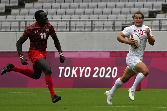 Madison Hughes of the U.S. is chased by Kenya's Collins Injera as he runs down the pitch to score a try, in their men's rugby sevens match at the 2020 Summer Olympics, Monday, July 26, 2021 in Tokyo, Japan. (AP Photo/Shuji Kajiyama)