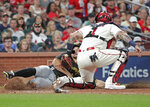 Pittsburgh Pirates' Bryan Reynolds, left, is tagged out at the plate by St. Louis Cardinals catcher Yadier Molina (4) after trying to score from first on a single by Yoshi Tsutsugo in the seventh inning of a baseball game, Saturday, Aug. 21, 2021, in St. Louis. (AP Photo/Tom Gannam)