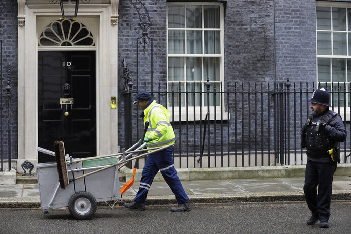 A cleaner works in Downing Street in London, Thursday, March 14, 2019. In a tentative first step toward ending months of political deadlock, British lawmakers voted Wednesday to block the country from leaving the European Union without a divorce agreement, triggering an attempt to delay that departure, currently due to take place on March 29.(AP Photo/Kirsty Wigglesworth)