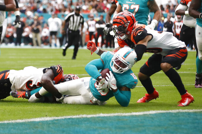 Cincinnati Bengals strong safety Shawn Williams (36) and free safety Jessie Bates (30) tackle Miami Dolphins wide receiver Albert Wilson (15) just short of the end zone, during the first half at an NFL football game, Sunday, Dec. 22, 2019, in Miami Gardens, Fla. (AP Photo/Brynn Anderson)