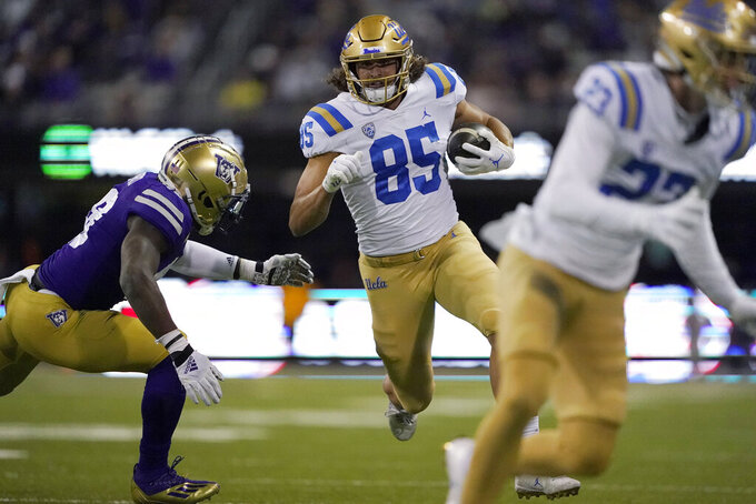 UCLA tight end Greg Dulcich (85) carries the ball as Washington linebacker Edefuan Ulofoshio, left, closes in during the second half of an NCAA college football game Saturday, Oct. 16, 2021, in Seattle. UCLA won 24-17. (AP Photo/Ted S. Warren)