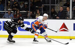 New York Islanders' Anthony Beauvillier, right, takes a shot on goal as Los Angeles Kings' Drew Doughty, left, closes in during the first period of an NHL hockey game Wednesday, Nov. 27, 2019, in Los Angeles. (AP Photo/Marcio Jose Sanchez)