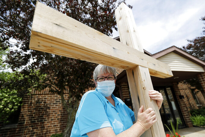 """Associate Pastor Sharon Rogers poses for a portrait with a cross at Light of Christ Lutheran Church in Algonquin, Ill., Sunday, May 24, 2020. """"The church is not a building, the church is people,"""" said Rogers, explaining why parents had embraced the idea of an outdoor service for their children's upcoming confirmation ceremony. (AP Photo/Nam Y. Huh)"""