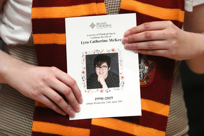 A mourner wearing a  Harry Potter Gryffindor House scarf holds an order of service as she arrives for the funeral of slain journalist Lyra McKee at St Anne's Cathedral in Belfast, Northern Ireland, Wednesday April 24, 2019.  The leaders of Britain and Ireland will join hundreds of mourners Wednesday at the funeral of Lyra McKee, the young journalist shot dead during rioting in Northern Ireland last week. (Brian Lawless/PA via AP)