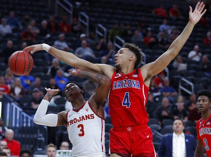 Arizona's Chase Jeter (4) tries to block a shot by Southern California's Elijah Weaver during the first half of an NCAA college basketball game in the first round of the Pac-12 conference tournament Wednesday, March 13, 2019, in Las Vegas. (AP Photo/John Locher)
