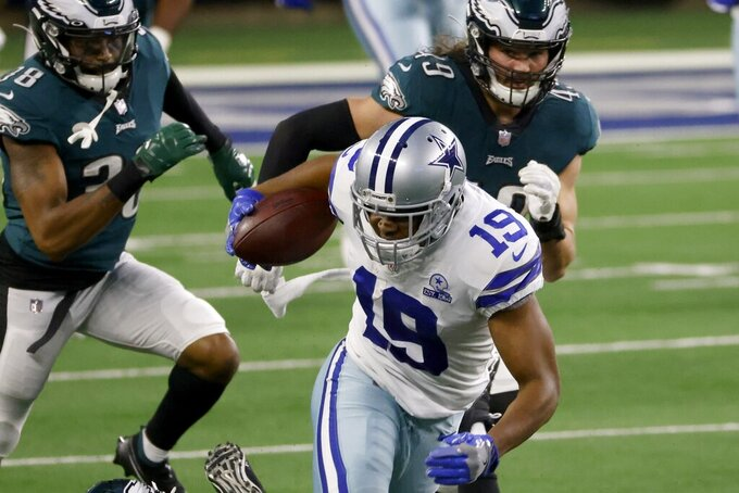 Dallas Cowboys wide receiver Amari Cooper (19) gains long yardage after a catch as Philadelphia Eagles cornerback Michael Jacquet (38) and Alex Singleton (49) gives pursuit in the second half of an NFL football game in Arlington, Texas, Sunday, Dec. 27. 2020. (AP Photo/Ron Jenkins)