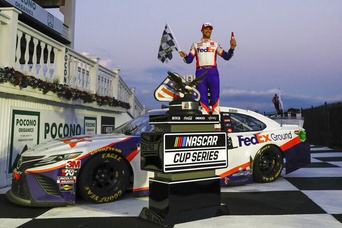 Denny Hamlin celebrates after winning the NASCAR Cup Series auto race at Pocono Raceway, Sunday, June 28, 2020, in Long Pond, Pa. (AP Photo/Matt Slocum)