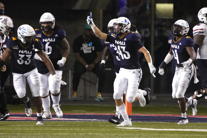 Northern Arizona defensive back Brady Shough (43) celebrates with teammates after scoring a touch down off an interception against Arizona during the first half of an NCAA college football game, Saturday, Sept. 18, 2021, in Tucson, Ariz. (AP Photo/Rick Scuteri)