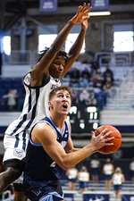 Villanova guard Collin Gillespie (2) looks to shoot under Butler guard Chuck Harris (3) in the first half of an NCAA college basketball game in Indianapolis, Sunday, Feb. 28, 2021. (AP Photo/Michael Conroy)