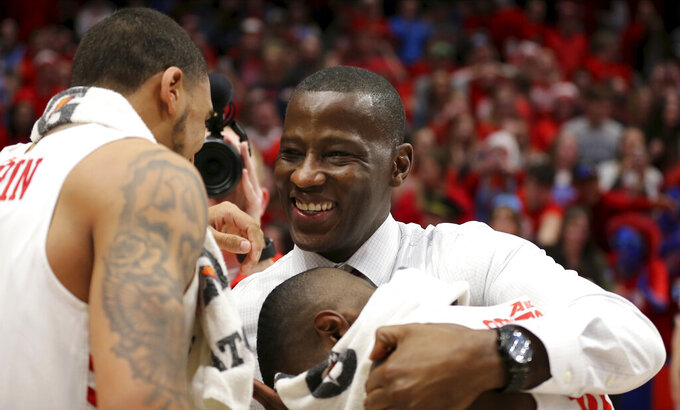 FILE - In this March 7, 2020, file photo, Dayton head coach Anthony Grant celebrates with Obi Toppin, left, and Jalen Crutcher, bottom right, after their win in an NCAA college basketball game against George Washington, in Dayton, Ohio. Toppin and Grant have claimed top honors from The Associated Press after leading the Flyers to a No. 3 final ranking. Toppin was voted the AP men's college basketball player of the year, Tuesday, March 24, 2020. Grant is the AP coach of the year. (AP Photo/Tony Tribble, File)