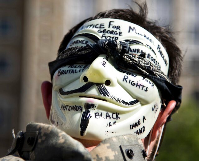 A demonstrator wears a mask during a peaceful protest in Ann Arbor, Mich. on Tuesday, June 2, 2020. Ann Arbor police chief Michael Cox and other officers walked with demonstrators marching for justice for George Floyd, who died after being restrained by Minneapolis police officers on May 25. (Jenna Kieser/Ann Arbor News via AP)