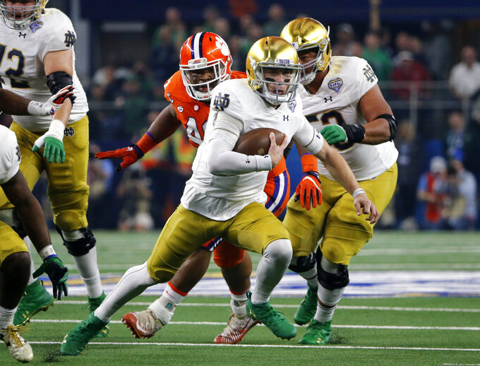 Notre Dame quarterback Ian Book (12) runs the ball for a gain in the first half of the NCAA Cotton Bowl semi-final playoff football game against Clemson on Saturday, Dec. 29, 2018, in Arlington, Texas. (AP Photo/Michael Ainsworth)