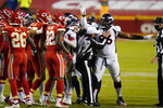Referee Alex Kemp (55) holds Denver Broncos defensive end Shelby Harris (96) back from Kansas City Chiefs players in the first half of an NFL football game in Kansas City, Mo., Sunday, Dec. 6, 2020. (AP Photo/Jeff Roberson)